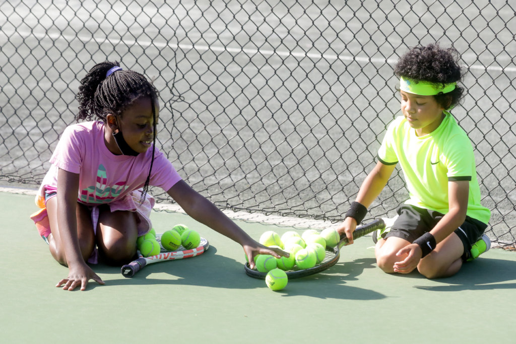 2 kids playing with tennis balls on a tennis court